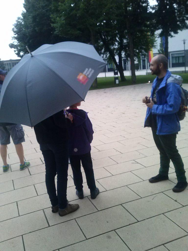 Mensch ohne Schirm spricht mit Mensch mit Schirm über Judo